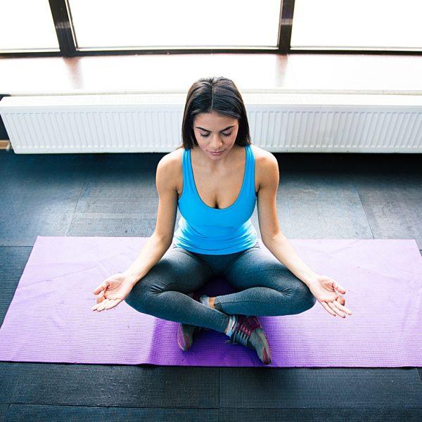 Young woman meditating on yoga mat at gym